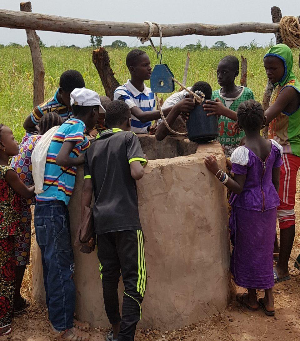 Niños sacando agua de un pozo instalado por Acción Senegal